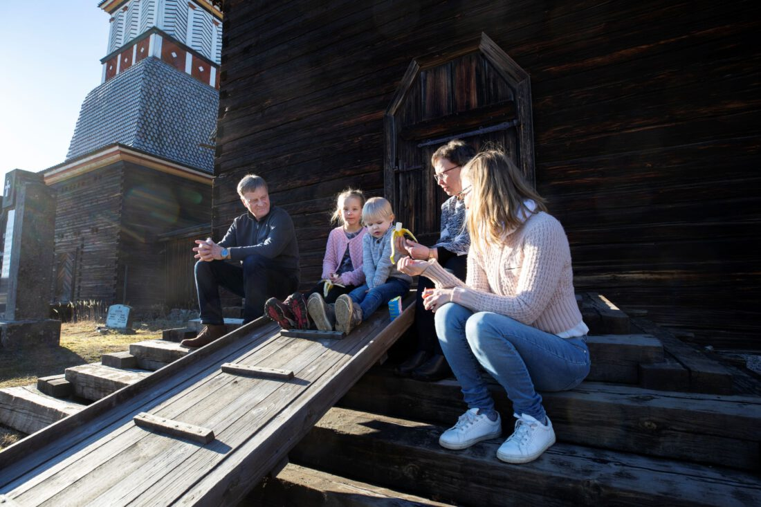 ihmisiä syömässä eväitä Petäjäveden vanhan kirkon portailla